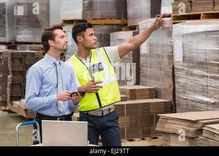 Warehouse worker showing something to his manager - Stock Photo
