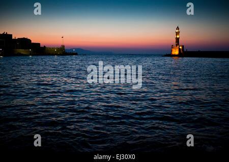 Sunset over Chania port promenade in Chania in Crete, Greece. - Stock Photo