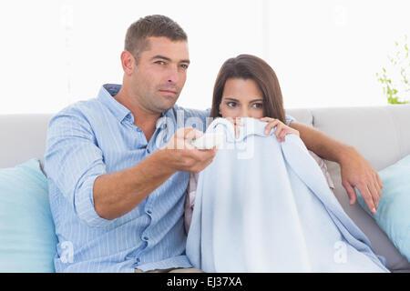 Couple watching horror movie on sofa - Stock Photo
