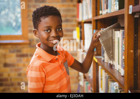 Portrait of boy selecting book in library - Stock Photo
