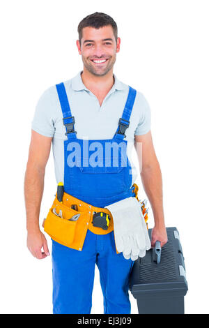 Happy workman in overalls holding toolbox - Stock Photo