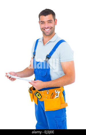 Happy carpenter in overalls holding clipboard - Stock Photo