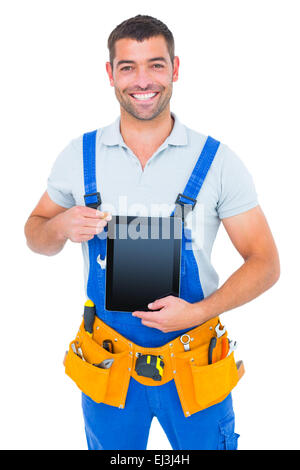 Happy repairman in overalls holding digital tablet - Stock Photo