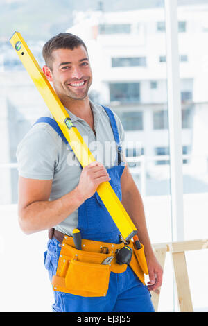 Happy repairman in overalls holding spirit level in office - Stock Photo