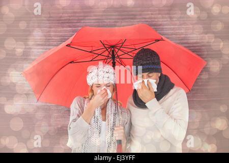 Composite image of couple in winter fashion sneezing under umbrella - Stock Photo