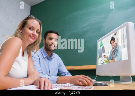 Composite image of artist drawing something on graphic tablet with colleagues behind - Stock Photo