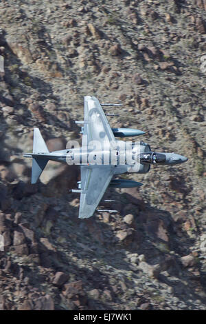 Close Up Photo Of A US Marine Corps AV-8B Harrier Jet Fighter Flying At Low Altitude Along A Desert Valley In California, - Stock Photo