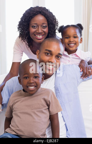 Happy family sitting on the couch together - Stock Photo