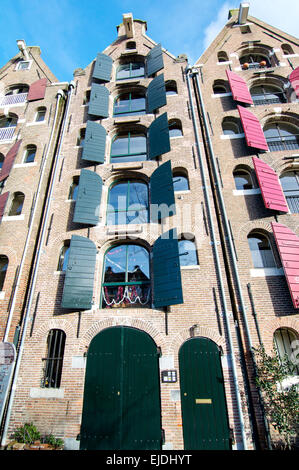 A 6 level high canalside building in Amsterdam. Formerly warehouses, these have been converted to residences. - Stock Photo