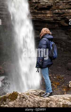 Woman hiker looking at Hardraw Force waterfall, North Yorkshire Dales, England UK - Stock Photo