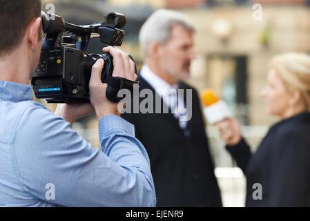 Cameraman Recording Female Journalist Interviewing Businessman - Stock Photo