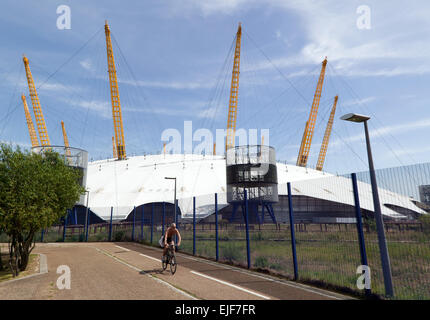 A lone cyclist on the Thames path around  the Greenwich peninsular, with the O2 arena in ther background - Stock Photo