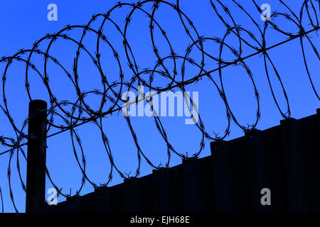 sharp razor wire on top of a metal fence silhouetted against the night sky - Stock Photo