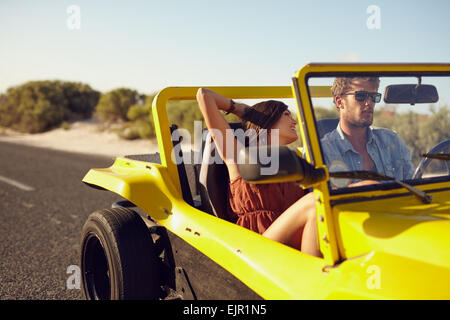 Romantic young couple on a road trip in a car. Caucasian young man and woman going on a holiday in a car. - Stock Photo
