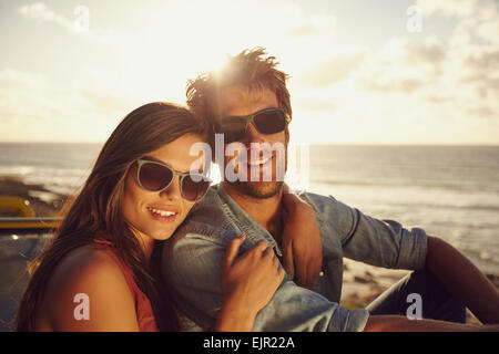 Portrait of beautiful young couple wearing sunglasses looking at camera while on a road trip. Young man and woman. - Stock Photo