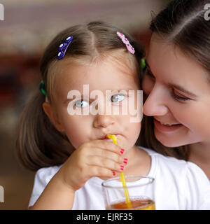 Closeup facial portrait of a little girl drinking juice through a straw next to her mother. Shallow depth of field. - Stock Photo