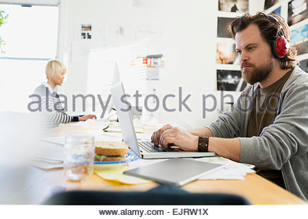 Designer with headphones working at laptop in office - Stock Photo