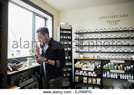 Man smelling essential oils in apothecary shop - Stock Photo