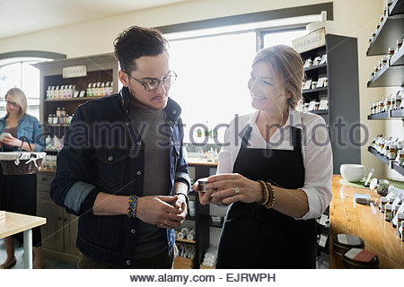 Apothecary shop owner helping man - Stock Photo