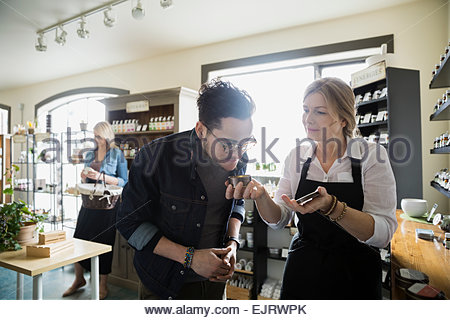 Apothecary shop owner letting man smell candle - Stock Photo