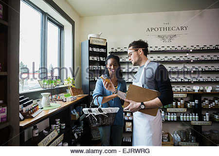 Apothecary shop owner showing customer product - Stock Photo