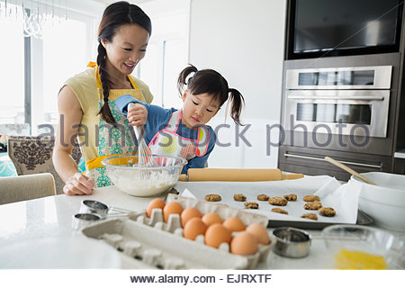 Mother and daughter baking cookies in kitchen - Stock Photo