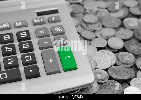 a desk Calculator with a green Equals button and Bank of england one pence and two pence Coins - Stock Photo