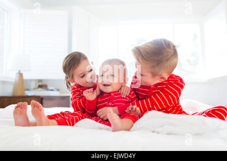 Boy (6-7) and girl (4-5) embracing brother (2-3) on bed - Stock Photo
