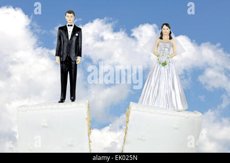 Bride and groom on split wedding cake with sky background. - Stock Photo