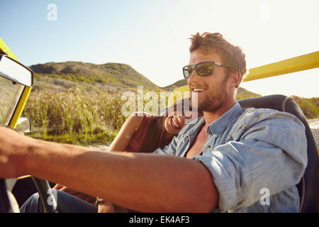 Happy young couple going on holidays together in a buggy car. Loving couple enjoying on a road trip. - Stock Photo
