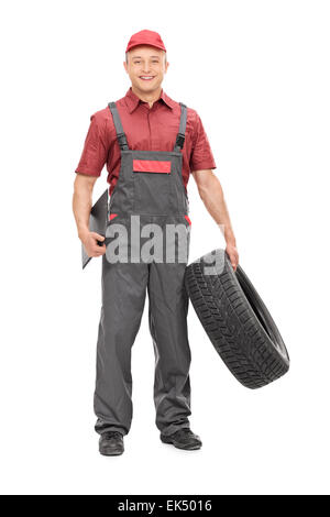 Full length portrait of a joyful mechanic in a gray jumpsuit, holding a tire in one hand and a clipboard in the - Stock Photo