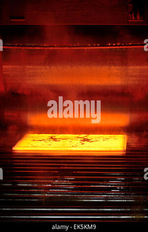 hot steel on conveyor inside of plant - Stock Photo