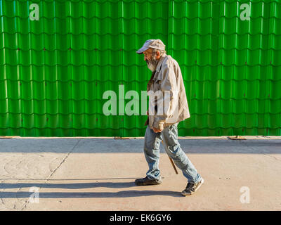 A male Hispanic senior citizen with a beard and wearing a baseball type hat, a soiled jacket and blue jeans walks - Stock Photo
