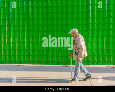 A male Hispanic senior citizen walks with a cane beside a bright green wall made of many tiles yielding a repetition - Stock Photo