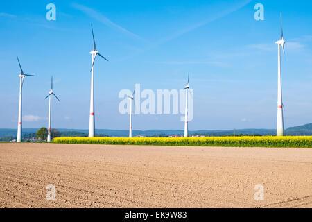 Many windwheels standing behind a barren field - Stock Photo