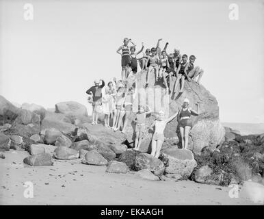 Antique c1910 photograph, boys and girls on a large boulder at the beach, Rockport, Massachusetts, USA. SOURCE: - Stock Photo