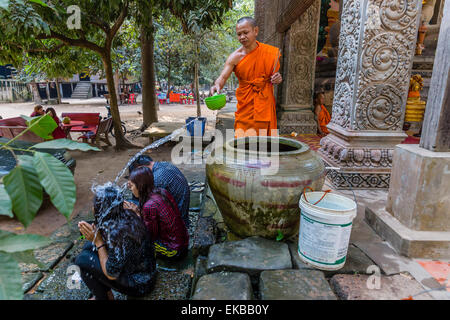 Buddhist monk offers water blessing near Prasat Bayon, Angkor Thom, Angkor, Siem Reap Province, Cambodia, Indochina, - Stock Photo