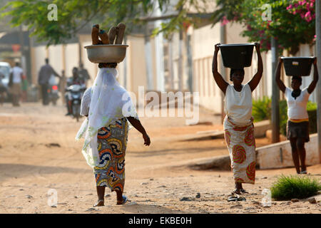 African women carrying large bowls on their heads, Lome, Togo, West Africa, Africa - Stock Photo