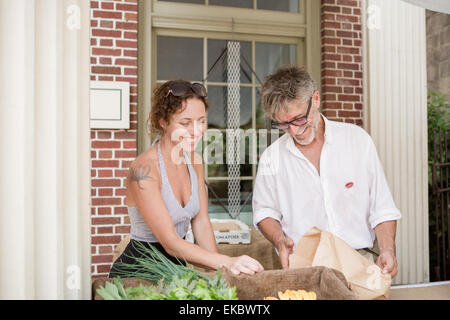 Farmers selling organic vegetables on stall outside store - Stock Photo