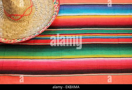 Mexican fiesta poncho rug in bright colors with sombrero background with copy space blanket b - Stock Photo