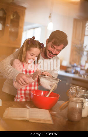 Father and daughter sifting flour into mixing bowl - Stock Photo