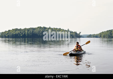 Father and son kayaking on lake, Ontario, Canada - Stock Photo