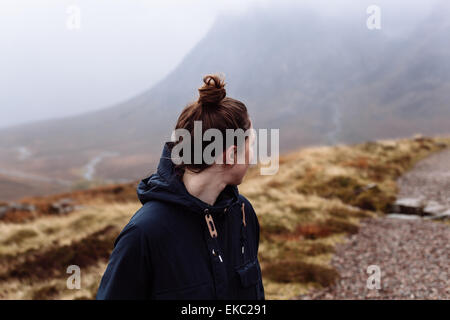 Woman looking over shoulder towards mountains - Stock Photo