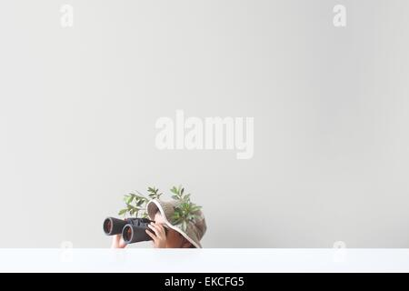 Boy looking through binoculars with some leaves and tree branches stuck on his safari hat - Stock Photo