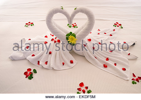 Bed decoration : two swans made of towels forming the shape of a heart - Stock Photo