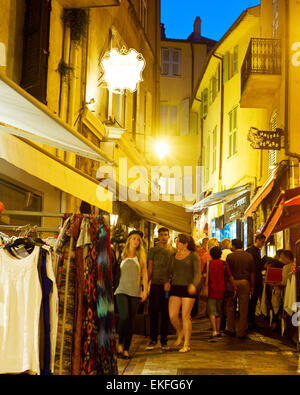 Tourists visit local shops in Cannes old city center. The city is famous for its luxury hotels an - Stock Photo