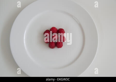 cluster red raspberries on plate - Stock Photo