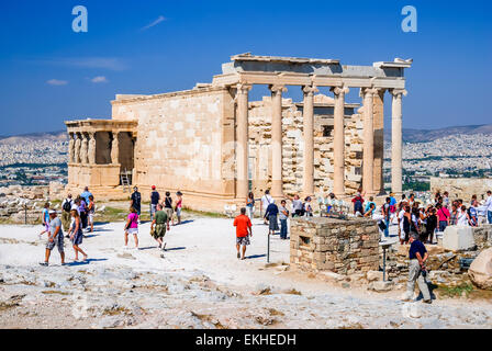Tourists at the famous Acropolis Hill enjoying Erechtheion temple monument in Athens, Greece. - Stock Photo