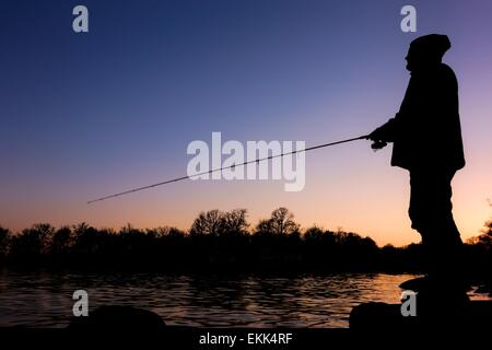 Silhouette of a fisherman standing on a rock by the Baltic Sea in Blekinge, Sweden. - Stock Photo