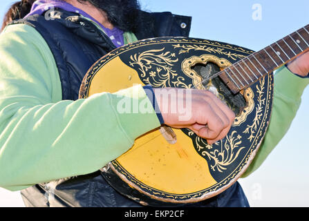 Street music entertainer playing mandolin with two strings - Stock Photo